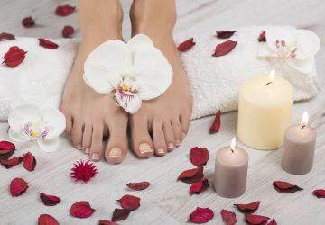 Schöne Füße mit french Maniküre auf weißen Handtuch. Orchidee blüht, roten Blüten und Kerzen um hölzerne Hintergrund. Spa, Fußpflege